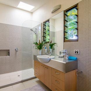 Foto di una stanza da bagno padronale tropicale di medie dimensioni con lavabo da incasso, ante lisce, ante in legno chiaro, top in acciaio inossidabile, doccia aperta, piastrelle a mosaico, pareti bianche, pavimento in gres porcellanato, piastrelle beige e doccia aperta