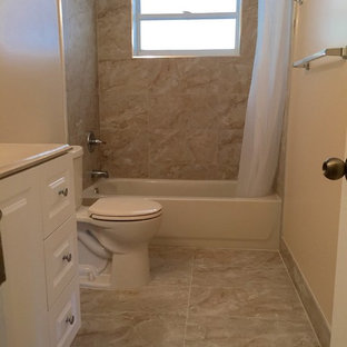 Mid-sized trendy beige tile and ceramic tile ceramic floor drop-in bathtub photo in Miami with white cabinets, a two-piece toilet, beige walls and an undermount sink