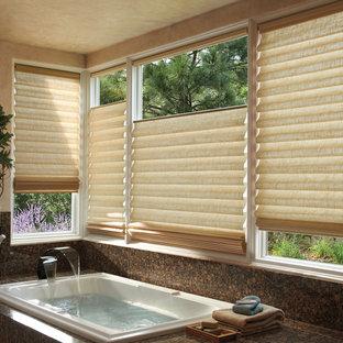 Immagine di una stanza da bagno padronale tropicale di medie dimensioni con vasca da incasso, piastrelle marroni, lastra di pietra e pareti beige