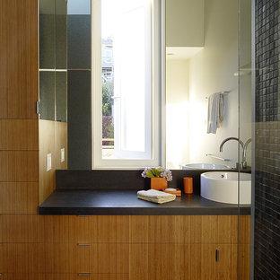 Imagen de cuarto de baño moderno con armarios con paneles lisos, suelo de madera clara, puertas de armario de madera oscura, paredes grises y encimera de esteatita