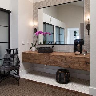 Diseño de cuarto de baño principal, contemporáneo, grande, con armarios abiertos, puertas de armario de madera en tonos medios, bañera esquinera, ducha empotrada, baldosas y/o azulejos beige, paredes grises, suelo de cemento, lavabo sobreencimera y encimera de madera