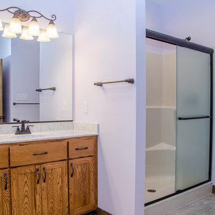 Immagine di una stanza da bagno padronale classica di medie dimensioni con ante lisce, ante in legno scuro, doccia alcova, WC monopezzo, pareti viola, pavimento in laminato, lavabo integrato, top in laminato, pavimento beige, porta doccia scorrevole e top beige