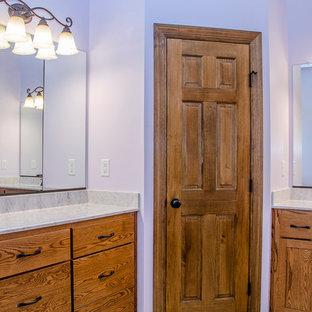 Esempio di una stanza da bagno padronale classica di medie dimensioni con ante lisce, ante in legno scuro, doccia alcova, WC monopezzo, pareti viola, pavimento in laminato, lavabo integrato, top in laminato, pavimento beige, porta doccia scorrevole e top beige