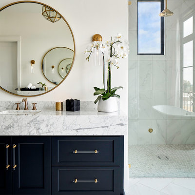 Bathroom - transitional master porcelain tile and white floor bathroom idea in Austin with recessed-panel cabinets, black cabinets, white walls, an undermount sink, quartz countertops, a hinged shower door and white countertops
