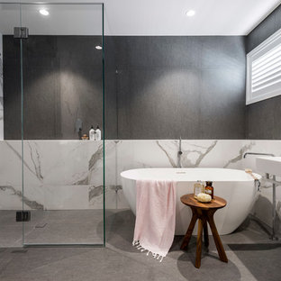 This is an example of a contemporary bathroom in Brisbane with a freestanding tub, a curbless shower, gray tile, white tile, grey walls, a vessel sink, grey floor, a hinged shower door and white benchtops.