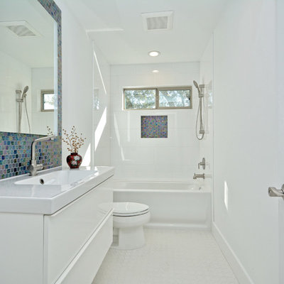 Example of a mid-sized eclectic master glass tile and multicolored tile bathroom design in Austin with flat-panel cabinets, white walls, medium tone wood cabinets, an undermount sink and quartz countertops
