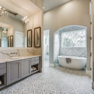 Modelo de cuarto de baño principal, de estilo de casa de campo, grande, sin sin inodoro, con armarios estilo shaker, puertas de armario grises, bañera exenta, baldosas y/o azulejos blancos, baldosas y/o azulejos grises, baldosas y/o azulejos de cerámica, paredes grises, suelo de azulejos de cemento, encimera de cuarzo compacto, suelo blanco y lavabo encastrado