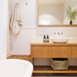 Photo of a country master bathroom in Wollongong with flat-panel cabinets, medium wood cabinets, a freestanding tub, white walls, a vessel sink, wood benchtops, beige floor and brown benchtops.
