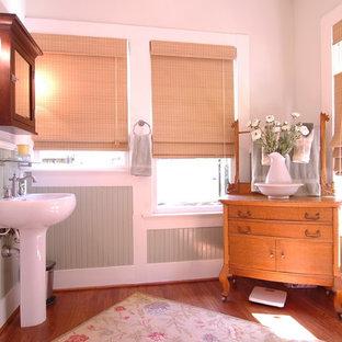 Ispirazione per una stanza da bagno con doccia tradizionale di medie dimensioni con lavabo a colonna, pareti bianche, pavimento in legno massello medio e pavimento marrone