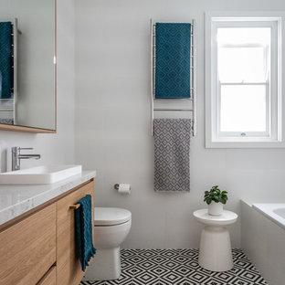 Diseño de cuarto de baño infantil, contemporáneo, con bañera empotrada, paredes blancas, lavabo encastrado, suelo multicolor, armarios tipo mueble, puertas de armario de madera clara, sanitario de pared, baldosas y/o azulejos blancos, baldosas y/o azulejos de cerámica, suelo de baldosas de cerámica, encimera de mármol y encimeras multicolor