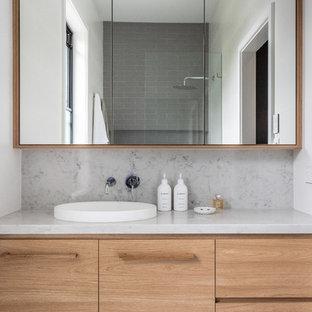 Новый формат декора квартиры: главная ванная комната в современном стиле с светлыми деревянными фасадами, серой плиткой, белыми стенами, накладной раковиной, разноцветным полом, фасадами островного типа, открытым душем, плиткой кабанчик, полом из керамической плитки, мраморной столешницей, открытым душем и разноцветной столешницей