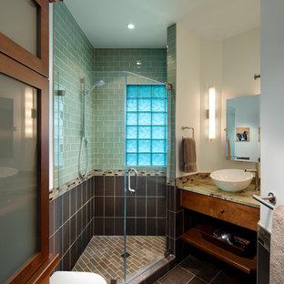 Bild på ett amerikanskt badrum, med ett fristående handfat, släta luckor, skåp i mörkt trä, en hörndusch, brun kakel, tunnelbanekakel, en vägghängd toalettstol, klinkergolv i keramik och brunt golv