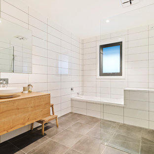 Contemporary wet room bathroom in Melbourne with flat-panel cabinets, medium wood cabinets, an alcove tub, white tile, a vessel sink, wood benchtops, grey floor, an open shower and brown benchtops.