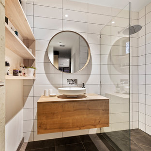 Photo of a small contemporary master wet room bathroom in Melbourne with raised-panel cabinets, medium wood cabinets, a two-piece toilet, white tile, ceramic tile, multi-coloured walls, ceramic floors, a vessel sink, wood benchtops, black floor, an open shower and brown benchtops.