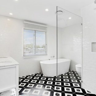 Design ideas for a beach style bathroom in Gold Coast - Tweed with white cabinets, a freestanding tub, white tile, ceramic tile, white walls, a drop-in sink, marble benchtops, multi-coloured floor, a hinged shower door and white benchtops.