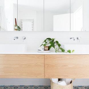 Inredning av ett maritimt badrum, med släta luckor, skåp i ljust trä, vita väggar, klinkergolv i porslin och ett fristående handfat