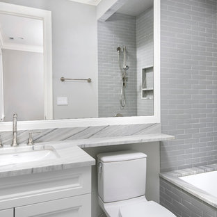 Inspiration for a large transitional master gray tile and stone slab marble floor alcove shower remodel in Chicago with an undermount sink, recessed-panel cabinets, white cabinets, marble countertops, an undermount tub and gray walls