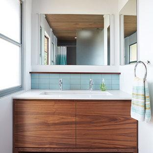 Idéer för 60 tals vitt badrum, med släta luckor, skåp i mellenmörkt trä, blå kakel, vita väggar, ett undermonterad handfat och grått golv