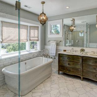 Ispirazione per una stanza da bagno padronale stile americano di medie dimensioni con ante con finitura invecchiata, vasca freestanding, doccia ad angolo, WC a due pezzi, piastrelle bianche, piastrelle diamantate, pareti grigie, pavimento in marmo, lavabo sottopiano e top in marmo