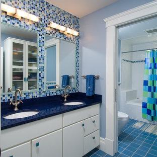 Exemple d'une salle de bain chic de taille moyenne pour enfant avec des portes de placard blanches, un carrelage bleu, carrelage en mosaïque, un placard à porte plane, une baignoire en alcôve, un combiné douche/baignoire, un WC séparé, un mur bleu, un sol en carrelage de céramique, un lavabo encastré, un plan de toilette en surface solide, un sol bleu et un plan de toilette bleu.
