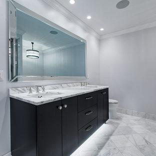 Idées déco pour un grand sauna classique avec un lavabo encastré, un placard à porte plane, des portes de placard en bois sombre, un plan de toilette en marbre, une baignoire encastrée, un WC à poser, un carrelage blanc, un carrelage de pierre, un mur blanc et un sol en marbre.
