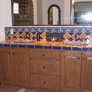 Inspiration for a medium sized mediterranean ensuite bathroom with raised-panel cabinets, medium wood cabinets, tiled worktops, blue tiles, yellow tiles, ceramic tiles, a corner bath, a walk-in shower, a one-piece toilet, a built-in sink, white walls and terracotta flooring.