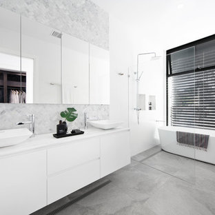 Photo of a contemporary master wet room bathroom in Melbourne with flat-panel cabinets, white cabinets, gray tile, white benchtops, a freestanding tub, white walls, a vessel sink, grey floor and an open shower.