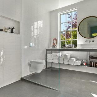Inredning av ett modernt vit vitt badrum, med en kantlös dusch, en vägghängd toalettstol, vit kakel, betonggolv, ett fristående handfat, grått golv och med dusch som är öppen
