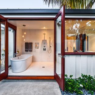 Foto di una stanza da bagno tropicale con vasca freestanding e doccia a filo pavimento