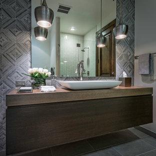 Ejemplo de cuarto de baño principal, rústico, grande, con armarios con paneles lisos, puertas de armario de madera en tonos medios, baldosas y/o azulejos grises, baldosas y/o azulejos de mármol, paredes grises, suelo de baldosas de porcelana, lavabo encastrado, encimera de madera y suelo gris