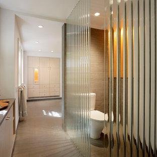 Modernes Badezimmer mit flächenbündigen Schrankfronten, hellen Holzschränken, Wandtoilette mit Spülkasten und beigefarbenen Fliesen in San Francisco
