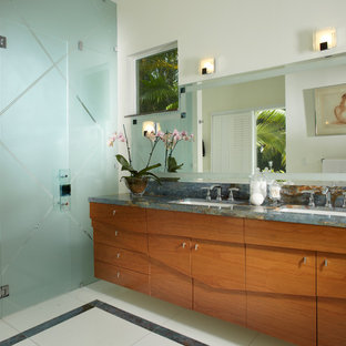 Photo of a small contemporary 3/4 bathroom in Miami with an undermount sink, furniture-like cabinets, light wood cabinets, marble benchtops, a drop-in tub, a double shower, a one-piece toilet, beige tile, glass tile, white walls and marble floors.