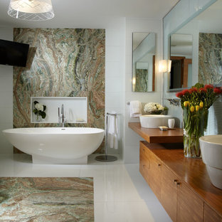 Inspiration for a large contemporary ensuite bathroom in Miami with a vessel sink, flat-panel cabinets, medium wood cabinets, wooden worktops, a freestanding bath, blue tiles, mosaic tiles and marble flooring.