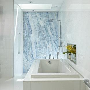 Modelo de cuarto de baño principal, actual, grande, con armarios con paneles lisos, puertas de armario blancas, bañera esquinera, ducha abierta, sanitario de una pieza, baldosas y/o azulejos multicolor, losas de piedra, paredes multicolor, suelo de mármol, lavabo encastrado y encimera de vidrio