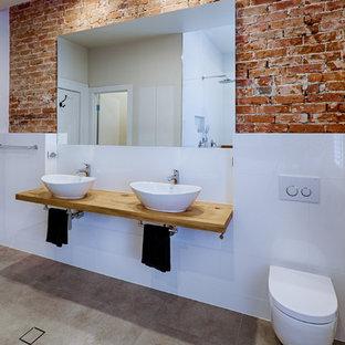 Diseño de cuarto de baño con ducha, industrial, grande, con armarios tipo mueble, baldosas y/o azulejos grises, baldosas y/o azulejos de porcelana, paredes blancas, suelo de baldosas de porcelana, encimera de madera, puertas de armario con efecto envejecido, bañera exenta, ducha abierta, sanitario de una pieza, lavabo suspendido, suelo gris, ducha abierta y encimeras marrones