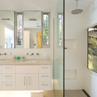 Photo of a mid-sized beach style bathroom in Sydney with white cabinets, white tile, ceramic tile, white walls, an undermount sink, engineered quartz benchtops, beige floor, an open shower, beige benchtops, flat-panel cabinets and a curbless shower.