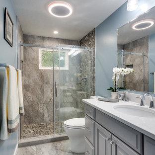 ワシントンD.C.の中くらいのトラディショナルスタイルのおしゃれなマスターバスルーム (レイズドパネル扉のキャビネット、グレーのキャビネット、アルコーブ型シャワー、分離型トイレ、グレーのタイル、石タイル、青い壁、セラミックタイルの床、アンダーカウンター洗面器、ラミネートカウンター) の写真