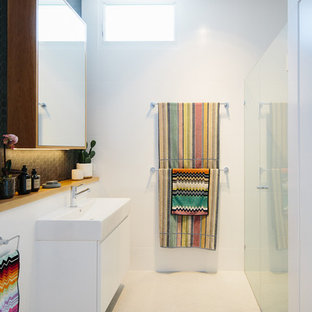 Contemporary bathroom in Other with flat-panel cabinets, white cabinets, a curbless shower, white tile, white walls, a console sink, white floor and a hinged shower door.