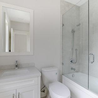 Foto di una piccola stanza da bagno per bambini contemporanea con ante in stile shaker, ante bianche, vasca ad angolo, vasca/doccia, WC monopezzo, lavabo sottopiano, top in granito e porta doccia a battente