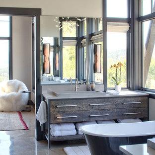 Modelo de cuarto de baño rural con armarios tipo mueble, puertas de armario de madera en tonos medios, paredes grises, suelo de cemento, lavabo encastrado, suelo gris y encimeras grises