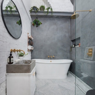 This is an example of a medium sized industrial bathroom in London with a freestanding bath, a walk-in shower, white walls, marble flooring, white cabinets, a one-piece toilet, a trough sink, marble worktops, multi-coloured floors and an open shower.