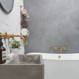 This is an example of an industrial bathroom in London with a freestanding bath, a walk-in shower, white walls and marble flooring.