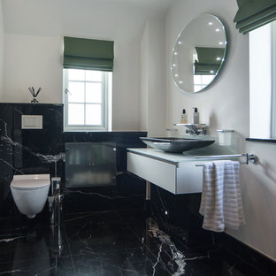 Inspiration for a large contemporary bathroom in London with a wall mounted toilet, black and white tiles, marble flooring, glass worktops, flat-panel cabinets, white cabinets, white walls and a vessel sink.