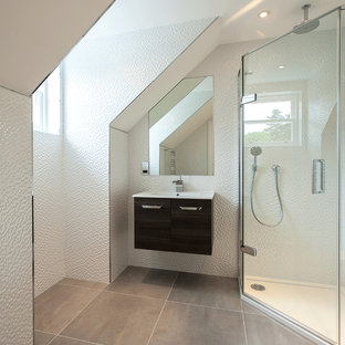 Photo of a contemporary bathroom in London with an integrated sink, flat-panel cabinets, black cabinets, a corner shower and white tiles.