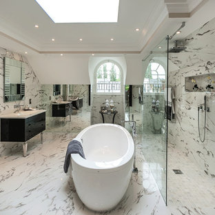 This is an example of a contemporary bathroom in London with a submerged sink, freestanding cabinets, black cabinets, a freestanding bath, a walk-in shower, beige tiles, an open shower and marble tiles.