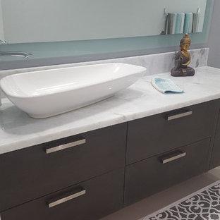 Ispirazione per una stanza da bagno con doccia etnica con ante lisce, doccia ad angolo, pavimento in gres porcellanato, lavabo a bacinella, top in marmo, porta doccia a battente, pareti blu e pavimento grigio