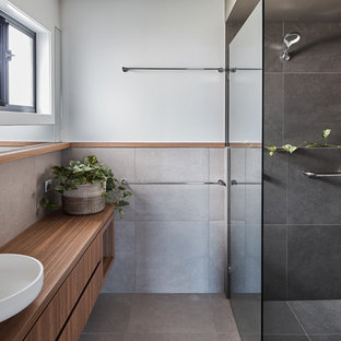 Inspiration for a medium sized beach style family bathroom in Gold Coast - Tweed with medium wood cabinets, a built-in bath, a walk-in shower, grey tiles, porcelain tiles, white walls, porcelain flooring, a vessel sink, laminate worktops, grey floors, an open shower and brown worktops.