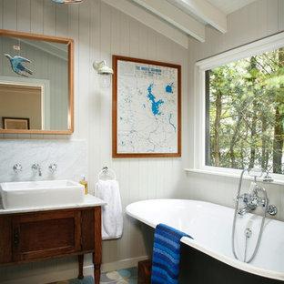 Klassisches Badezimmer mit verzierten Schränken, freistehender Badewanne, beigefarbenen Fliesen, blauen Fliesen, grauen Fliesen, weißer Wandfarbe und Aufsatzwaschbecken in London