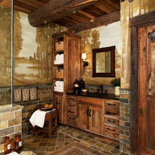 Example of a mid-sized mountain style master brown tile ceramic floor corner shower design in Detroit with an undermount tub, medium tone wood cabinets, shaker cabinets, multicolored walls and solid surface countertops