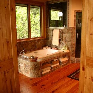 Ejemplo de cuarto de baño principal, rural, con ducha esquinera, baldosas y/o azulejos multicolor, paredes amarillas y suelo de madera en tonos medios